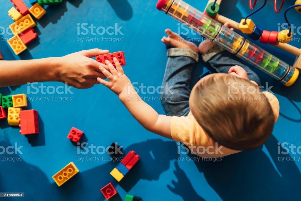 Bebé feliz jugando con bloques de juguete. - foto de stock