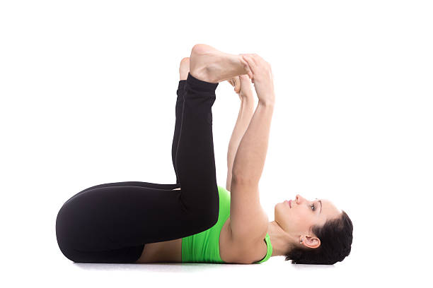 Happy Baby Pose Sporty girl on white background lying in yoga Happy Baby pose, Ananda Balasana, relaxing, aligning back, stretching spine, legs, relieving stress and fatigue apanasana stock pictures, royalty-free photos & images