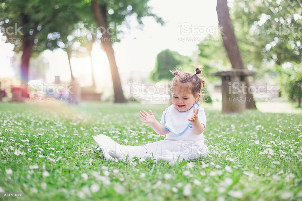 happy baby sitting on a grass and having fun stock photo