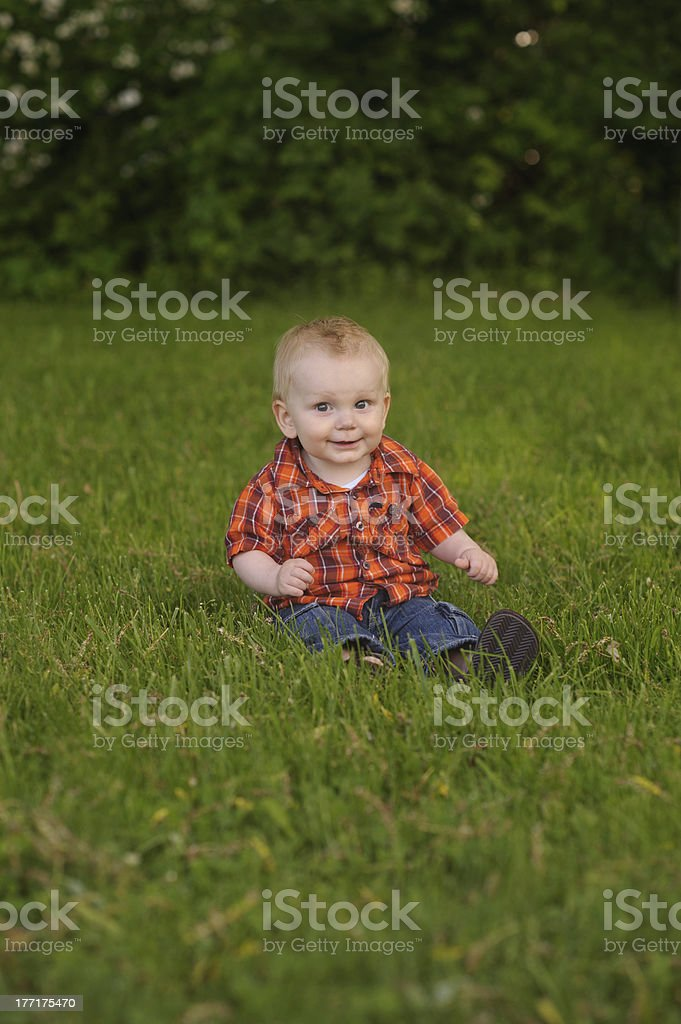 Happy Baby Sitting on Grass Outside royalty-free stock photo