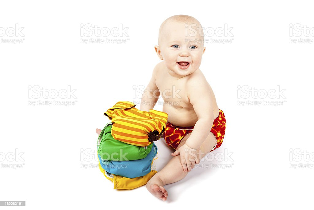 Happy baby sitting with stack of colorful cloth diapers royalty-free stock photo