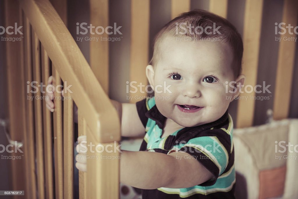 Happy baby standing up in his crib stock photo