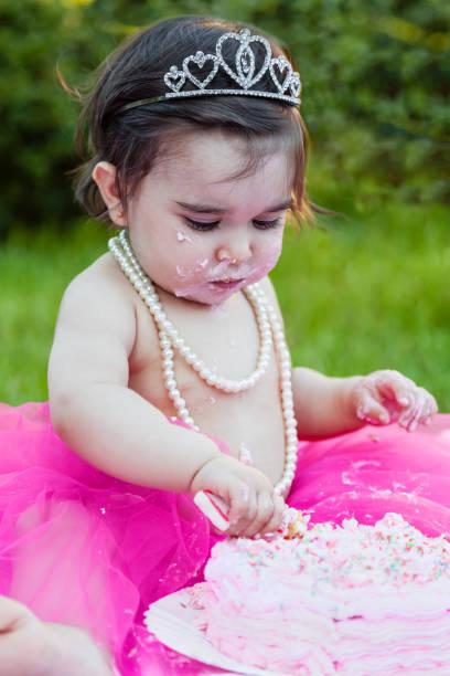 glückliches baby kleinkind mädchen im ersten geburtstag jubiläumsparty mit dreckiges gesicht ein chaos der rosa kuchen mit kerze. - prinzessinnen torte stock-fotos und bilder