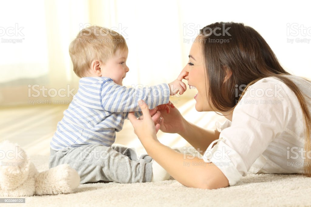 Happy baby touching his mother face stock photo