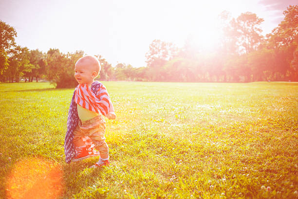 Happy baby wrapped in American flag on the Independence Day stock photo