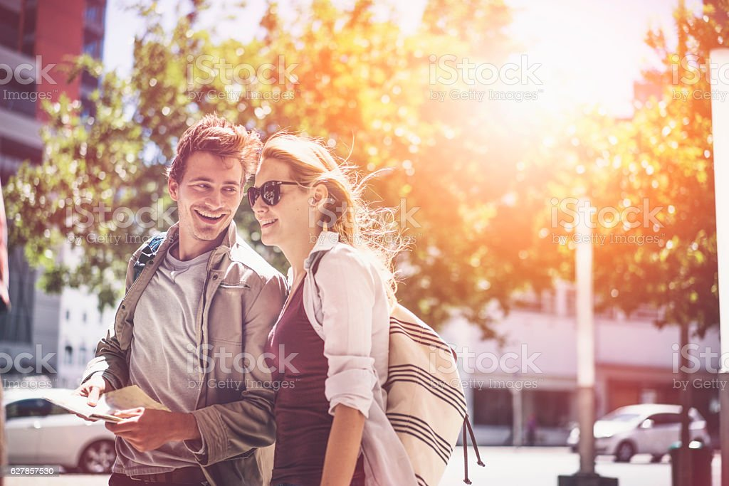 Happy backpackers traveling in city stock photo