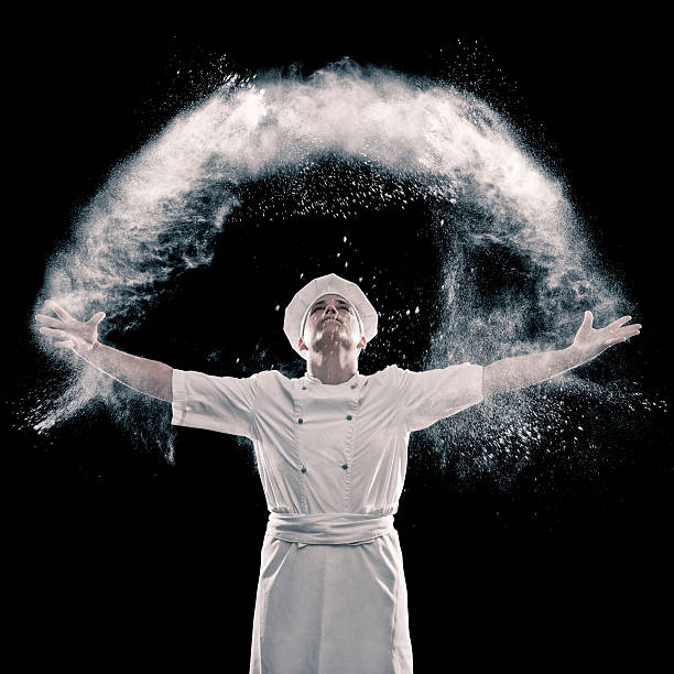 Happy baker Happy baker throwing flour chef's whites stock pictures, royalty-free photos & images