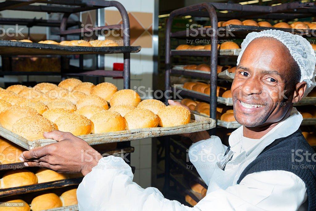 Happy baker showing his bread rolls stock photo