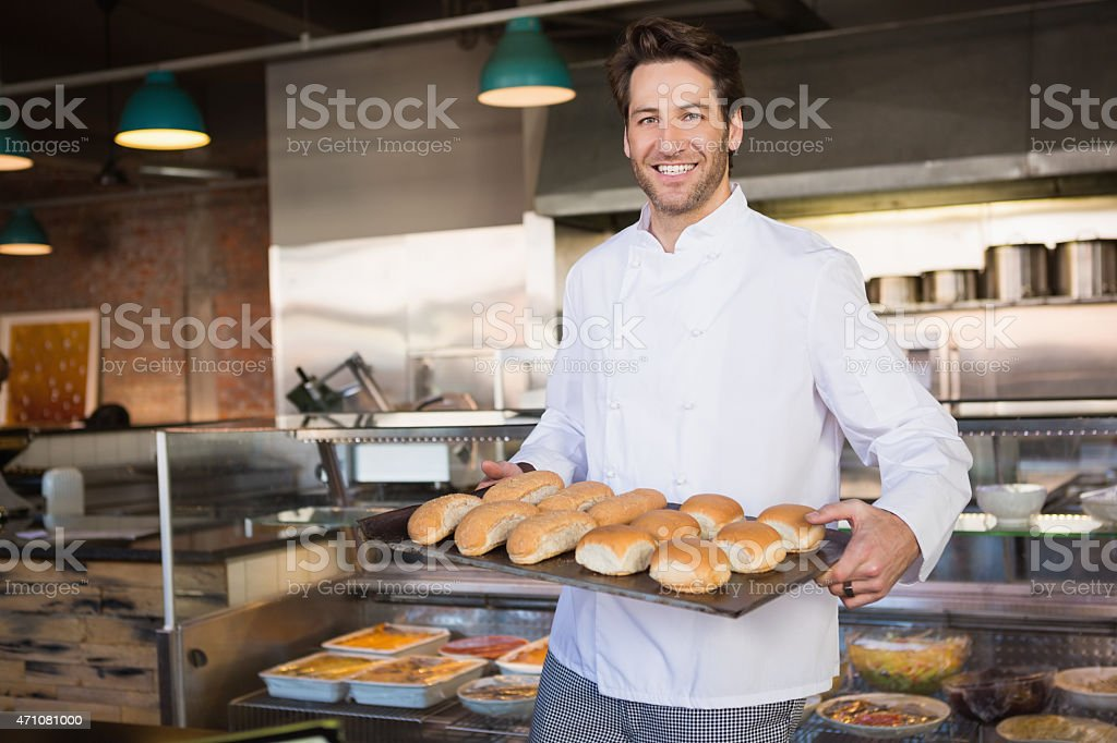 Happy baker showing tray with bread stock photo