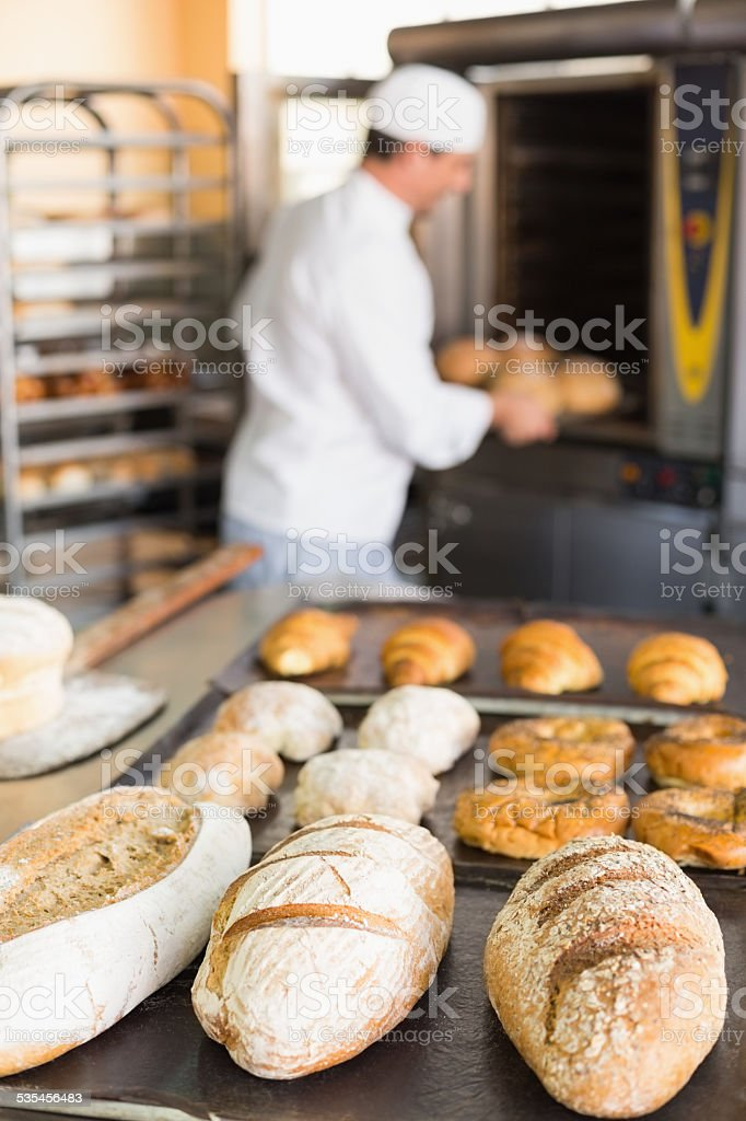 Happy baker taking out fresh loaves stock photo