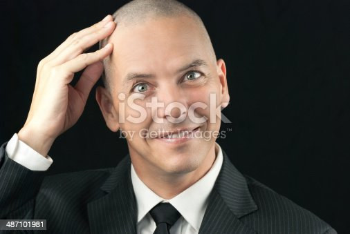 Close-up of a happy bald man feeling his shaved head.