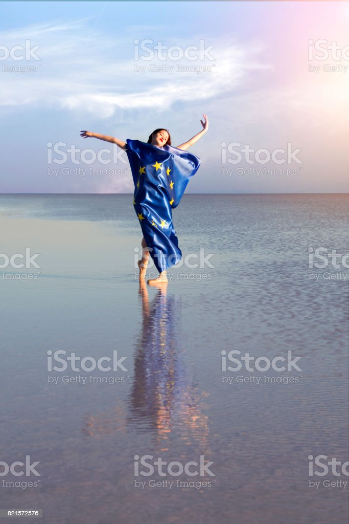 Happy ballerina on the water with European Union Flag a windy day. stock photo