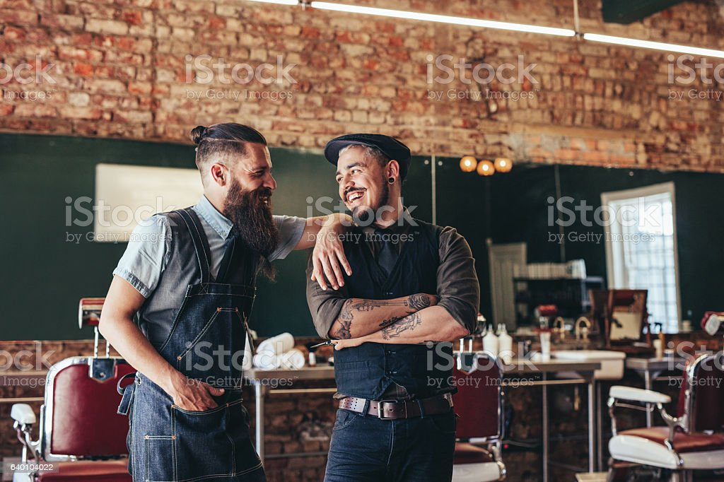 Happy barber with client standing at barbershop stock photo
