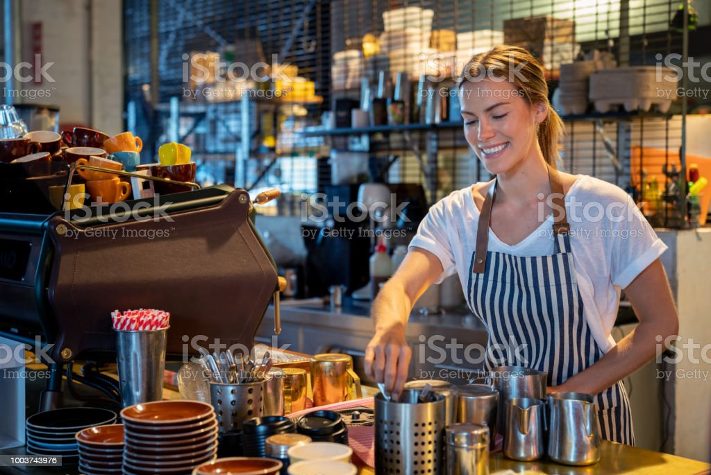 Happy barista making coffee at a cafe stock photo