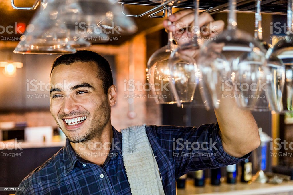 Happy bartender arranging wineglasses stock photo