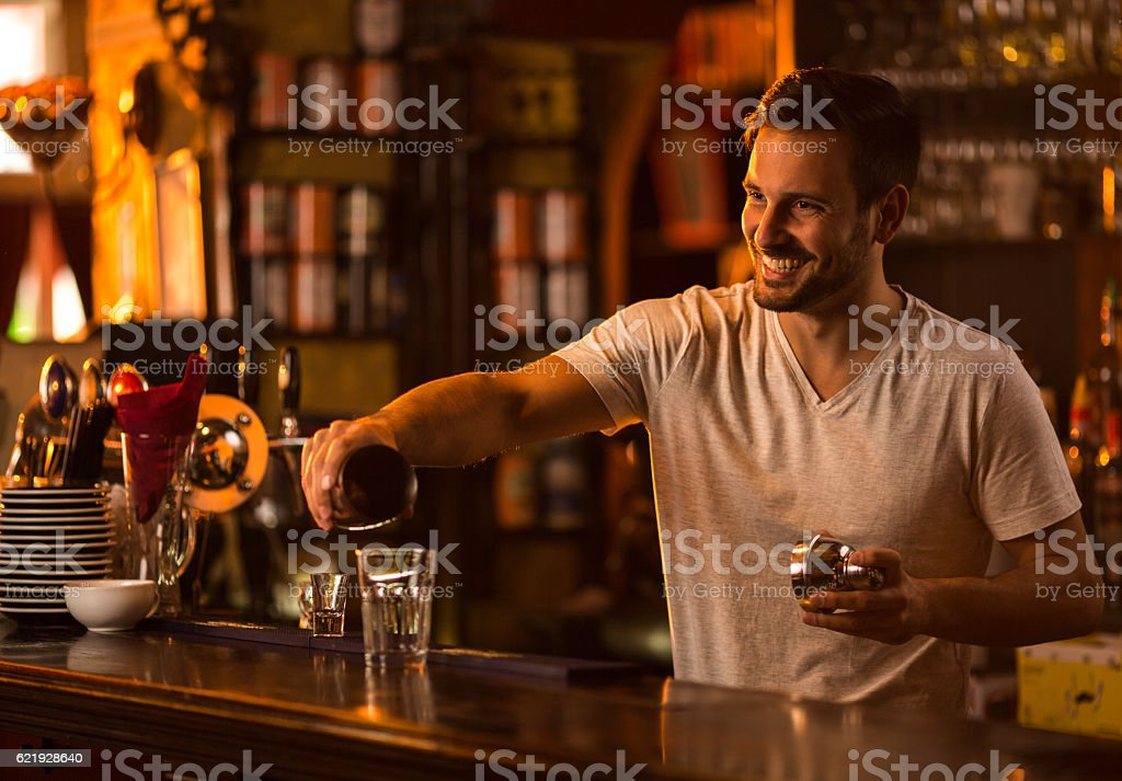 Happy bartender at bar counter preparing a cocktail. stock photo
