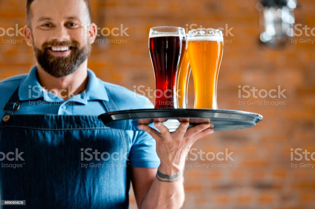 Happy bartender holding serving tray with glasses of beer Happy bearded bartender holding serving tray with glasses of beer, standing in the pub against brick wall. 25-29 Years Stock Photo