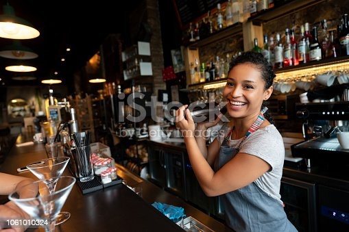 Portrait of a happy female bartender mixing drinks at a bar in a cocktail mixer
