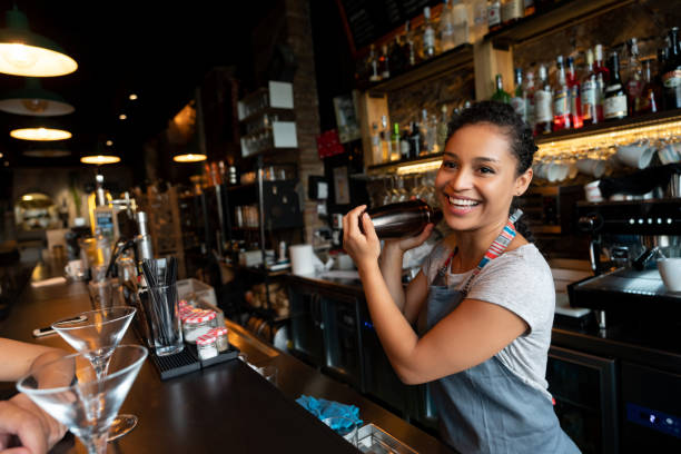 Happy bartender mixing drinks at the bar Portrait of a happy female bartender mixing drinks at a bar in a cocktail mixer bartender stock pictures, royalty-free photos & images