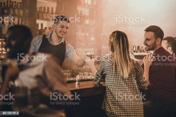 Happy bartender serving his customers with beer in a pub picture id931591814?b=1&k=6&m=931591814&s=612x612&h=qs70ppzzddx1nymoj9i0a6tx5srgfpqqzbnzjse7che=