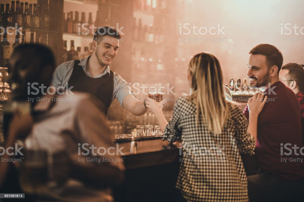 Happy bartender serving his customers with beer in a pub. стоковое фото