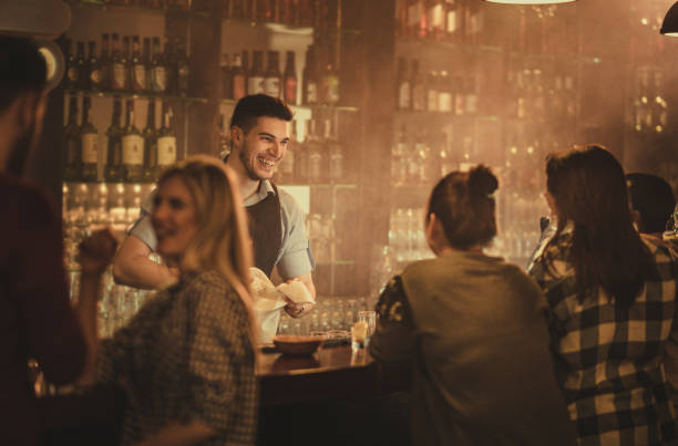 Happy bartender talking to his customers in a pub. Young happy waiter cleaning glasses and communicating with his customers in a bar. bartender stock pictures, royalty-free photos & images