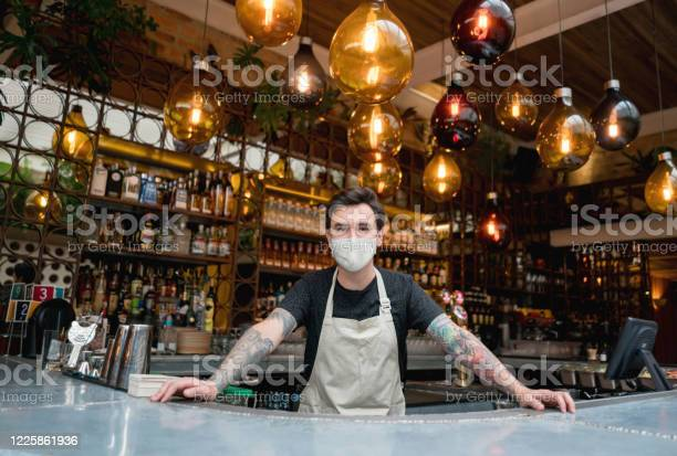 Happy bartender working at a bar wearing a facemask picture id1225861936?b=1&k=6&m=1225861936&s=612x612&h=nqo0z8aftua5zblnornvaij7ibgrfqxbiale3uinnnu=
