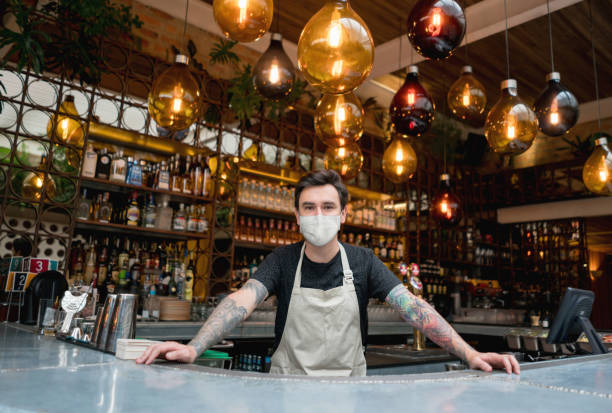 Happy bartender working at a bar wearing a facemask Happy bartender working at a bar wearing a facemask to avoid the spread of coronavirus – COVID-19 lifestyle concepts bartender stock pictures, royalty-free photos & images