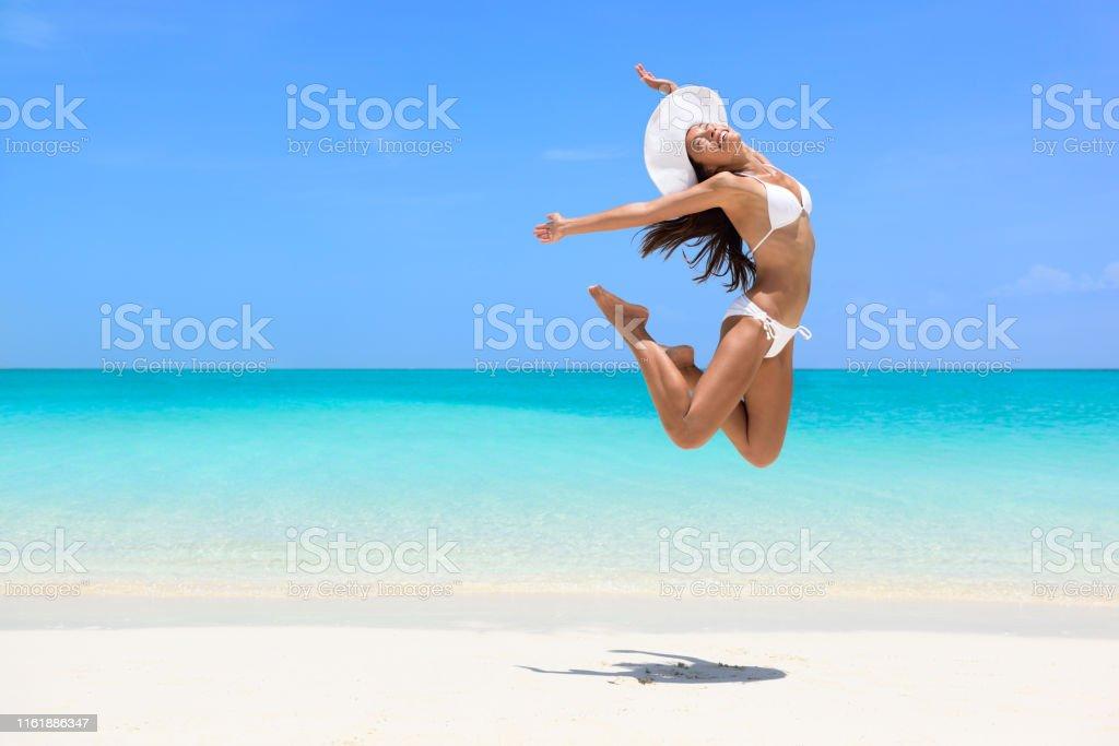 Happy bikini woman jumping of joy on beach. Excited holiday girl...