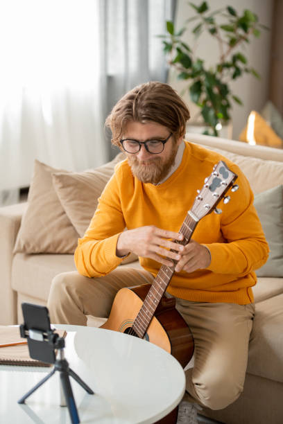 happy bearded blond guy with guitar teaching online audience how to play guitar - musicians singers during lockdown foto e immagini stock