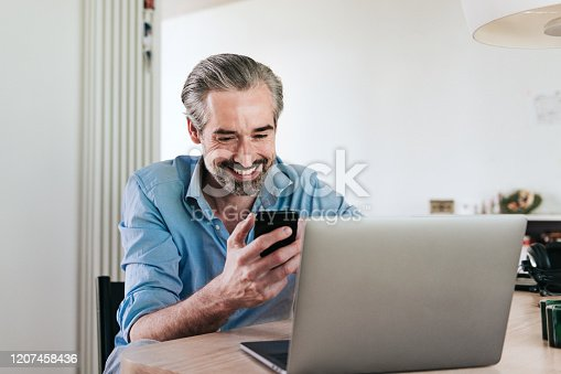 istock happy bearded business man looking at mobile in front of laptop 1207458436