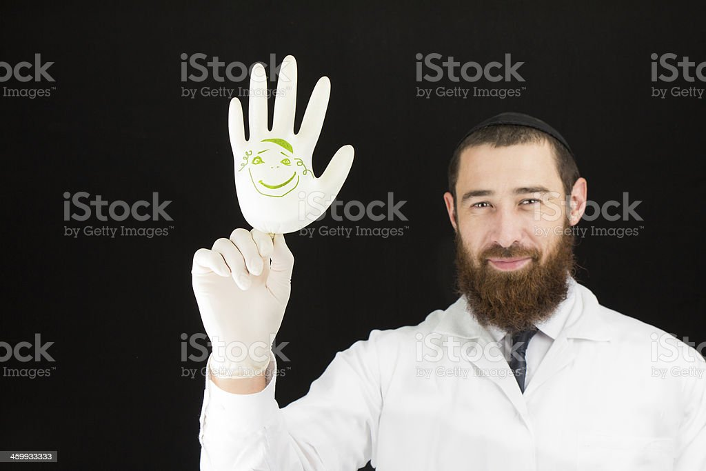 Happy Bearded Doctor Holding an Inflated Glove With a Drawing stock photo