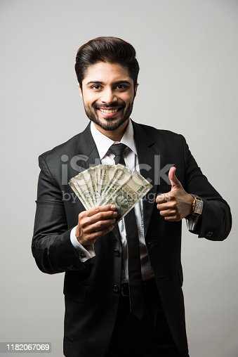 istock Happy bearded Indian businessman holding fan in hand, Indian Rupee currency bills of 500 , standing isolated over white background 1182067069