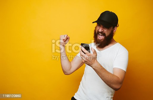 istock Happy bearded man celebrate success and looking at phone 1195120950