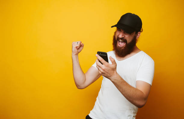 Happy bearded man celebrate success and looking at phone Happy bearded man celebrate success and looking at phone football fans stock pictures, royalty-free photos & images
