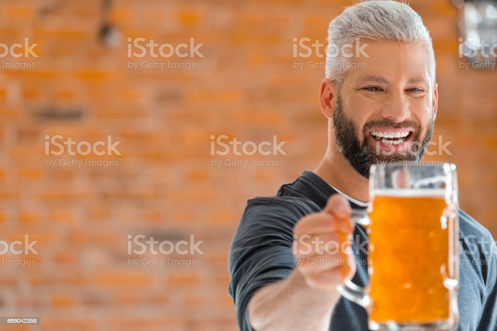 Happy bearded man holding mug of beer in pub Happy bearded man holding mug of beer, standing in the pub against brick wall. 35-39 Years Stock Photo