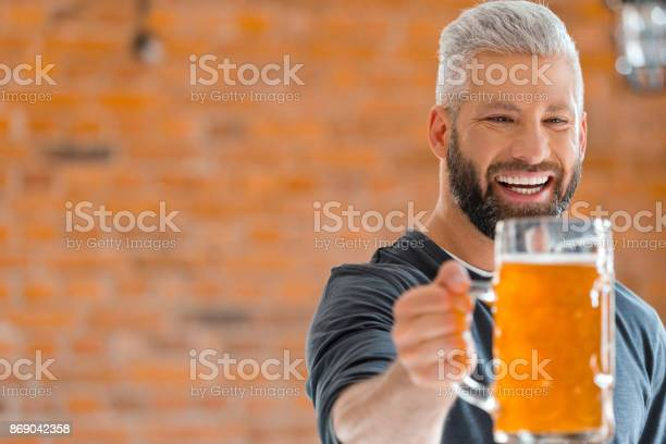 Happy Bearded Man Holding Mug Of Beer In Pub Stock Photo - Download Image Now