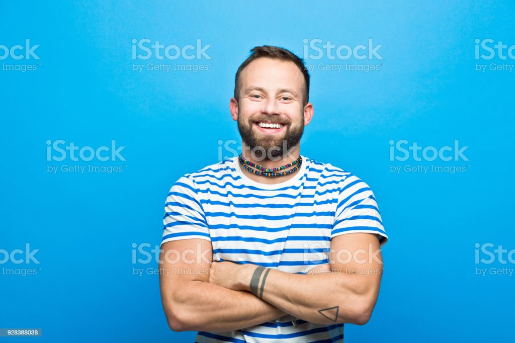 Happy bearded man in striped t-shirt, sailor style Portrait of happy bearded man wearing striped t-shirt smiling at camera. Studio shot, blue background. 30-34 Years Stock Photo