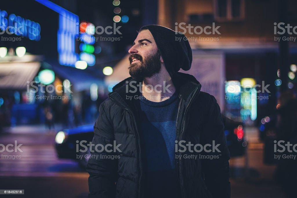 Happy bearded man in the city at night stock photo