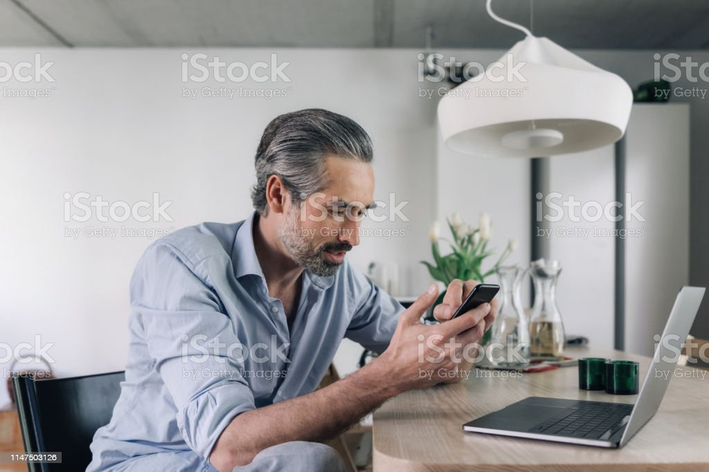 Relaxed handsome bearded man looking at mobile at home