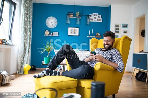 Young bearded mid adult man sitting in yellow armchair at apartment and using mobile phone and smiling
