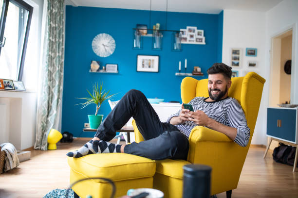 Happy bearded man sitting on armchair and using smart phone Young bearded mid adult man sitting in yellow armchair at apartment and using mobile phone and smiling armchair stock pictures, royalty-free photos & images