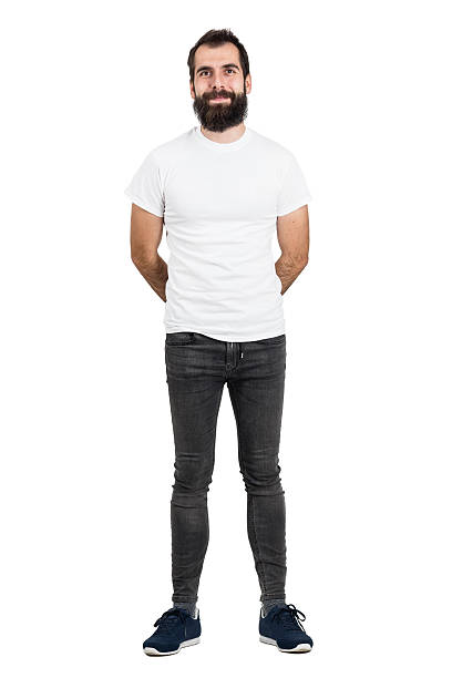 happy, bärtiger mann mit hände hinter dem rücken in weißen t-shirt - mann bart freisteller stock-fotos und bilder