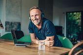 happy bearded midaged man with headphones listening music