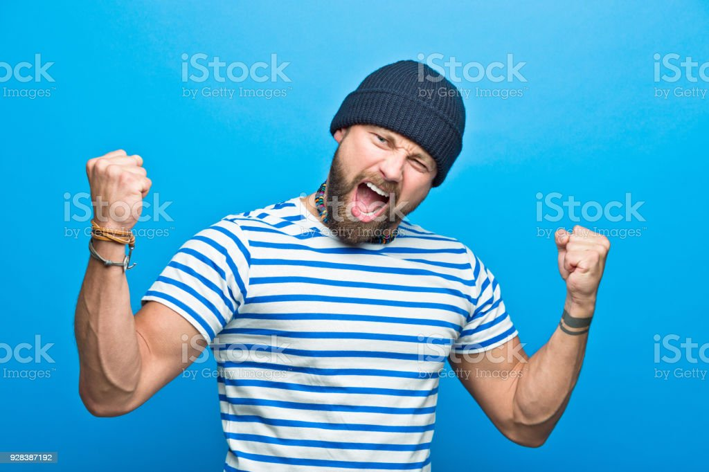 Happy bearded sailor flexing his muscles Portrait of happy bearded man wearing striped t-shirt and beanie hat flexing his muscles, screaming at camera. Studio shot, blue background. 30-34 Years Stock Photo