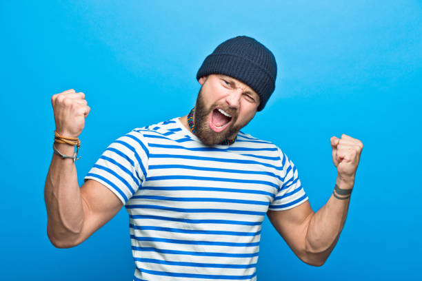 Happy bearded sailor flexing his muscles Portrait of happy bearded man wearing striped t-shirt and beanie hat flexing his muscles, screaming at camera. Studio shot, blue background. flexing muscles stock pictures, royalty-free photos & images
