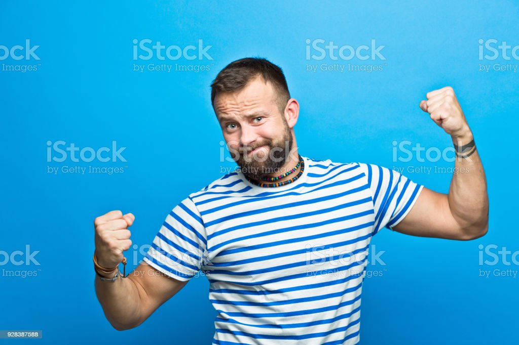 Happy bearded sailor flexing his muscles Portrait of happy bearded man wearing striped t-shirt flexing his muscles, smiling at camera. Studio shot, blue background. 30-34 Years Stock Photo