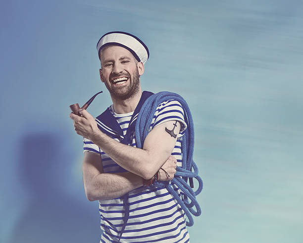 Happy bearded sailor man holding pipe and rope Portrait of happy bearded sailor man wearing white and blue striped clothing and sailor hat, holding a blue rope on shoulder and a pipe in hand. Standing against blue background, laughing at camera. Studio shot, one person. sailor stock pictures, royalty-free photos & images