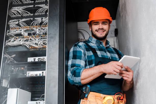 gelukkig bebaarde technicus in veiligheidshelm met digitale tablet - elektricien stockfoto's en -beelden