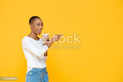 Happy beautiful African American woman drinking coffee smiling and pointing to empty space aside isolated on yellow background
